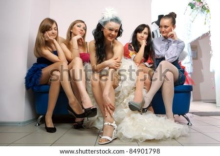 Bride sitting with envious girlfriend in professional fashion designer studio - stock photo