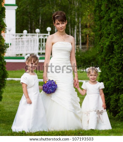 Bride stand with little girls in elegant dresses - stock photo