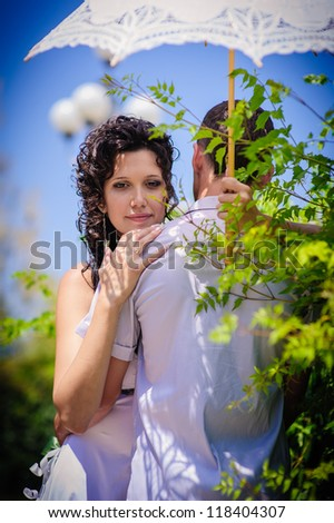 Bride standing near a bush in the park with umbrella. wedding dress. Bridal wedding bouquet of flowers. Love story of happy couple.feelings, relations, passion. - stock photo