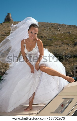 Bride standing on the automobile poses for the photographer - stock photo