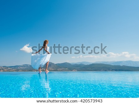 Bride standing on the edge on the infinity pool in Santorini Greece - stock photo