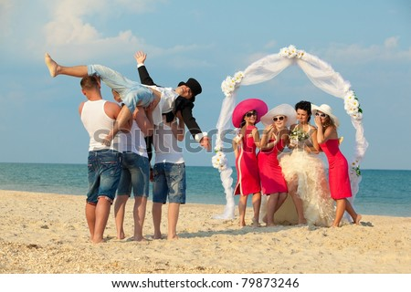 Bride standing with bridesmaids under archway on beach and waiting for her drunk groom - stock photo