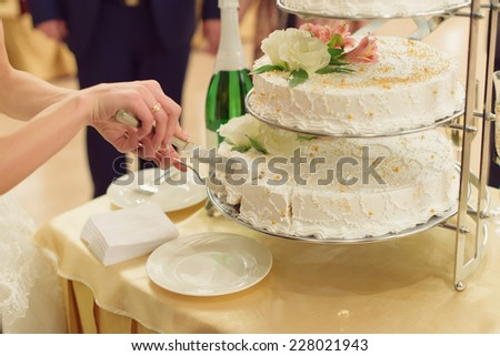 bride taking slice of wedding cake from tray - stock photo