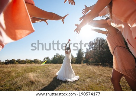Bride Throwing Bouquet For Guests To Catch - stock photo