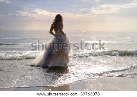 Bride walking along sea coast in the wedding dress - stock photo