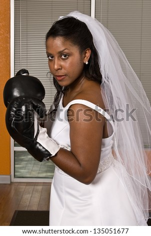 Bride wearing boxing gloves - stock photo