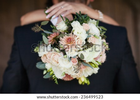Bride with a bouquet in the hands of the hugging groom - stock photo