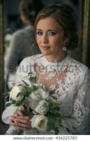 Bride with a perfect face sits behind a mirror holding a wedding bouquet in her tender arms - stock photo