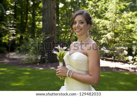 Bride with bouquet on her wedding day - stock photo