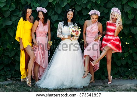 Bride with bridesmaids at  wedding walk outdoors - stock photo