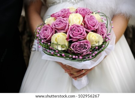 Bride with groom holding wedding bouquet at ceremony - stock photo