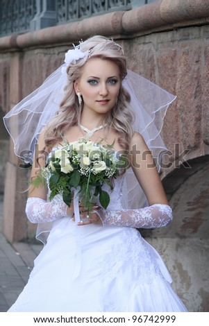 bride with  wedding bouquet.Against  stone wall. - stock photo