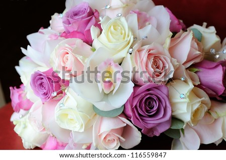 Brides bouquet of purple and pink roses and orchid - stock photo
