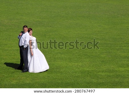 Brides on the pitch. green grass - stock photo