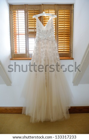 Brides wedding gown hanging up in window - stock photo