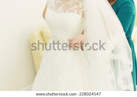 bridesmaid helping bride to button wedding dress - stock photo