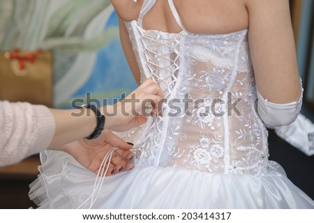 Bridesmaid helping the bride lacing up her dress closeup portrait - stock photo