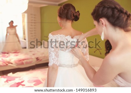 Bridesmaid helping the bride with the wedding dress - stock photo