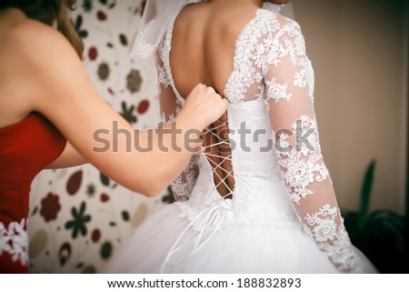 Bridesmaid helps bride to put on a wedding dress. - stock photo