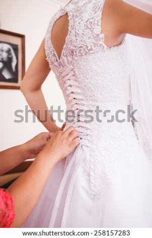 Bridesmaid helps to bride to put on wedding dress.  - stock photo