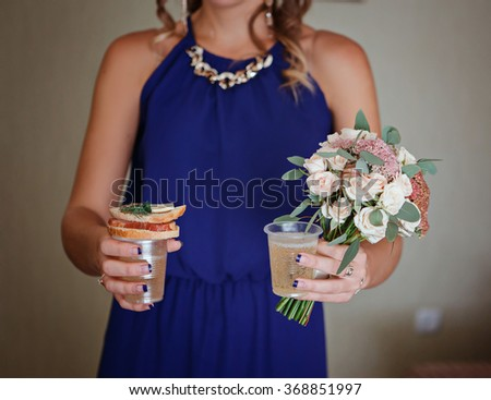 Bridesmaid holding a bouquet for the bride, a sandwich, glasses with champagne. Best Bridesmaids with food and champagne - stock photo