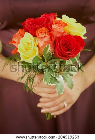 Bridesmaid holding autumn colored wedding bouquet of flowers - stock photo