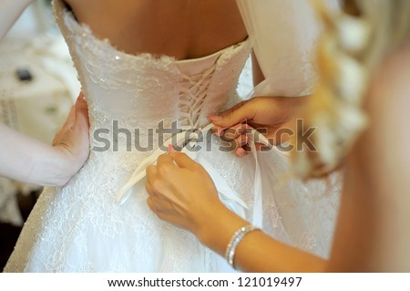 bridesmaid tying bow on wedding dress - stock photo