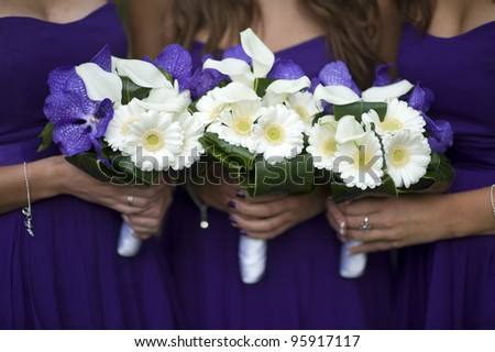 bridesmaids holding bouquets of white gerbera, white lilies and purple orchids - stock photo