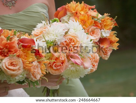Bridesmaids holding flower bouquets at wedding - stock photo