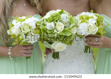 bridesmaids holding green wedding bouquets - stock photo
