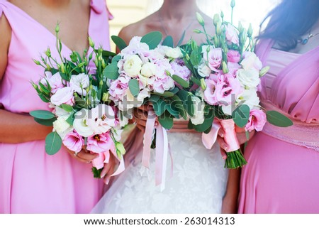 Bridesmaids in pink wedding outfit  holding bouquet of flowers on  ceremony . - stock photo