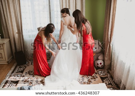 Bridesmaids in red dresses help bride prepare for her wedding - stock photo