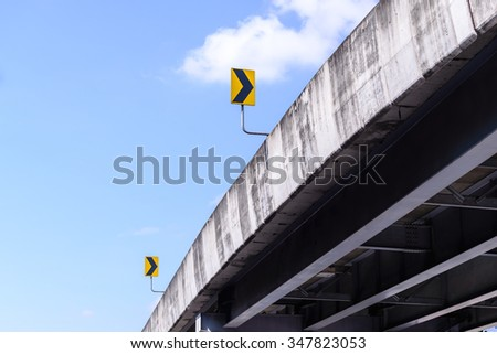 Bridge and right arrow sign with blue sky. - stock photo