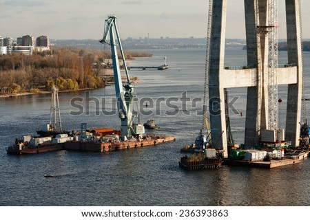 Bridge construction site with tower cranes - stock photo