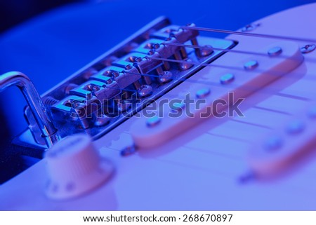 Bridge of a six string electric guitar with blue light - stock photo
