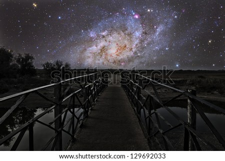 Bridge on a distant planet near the triangulum galaxy - stock photo