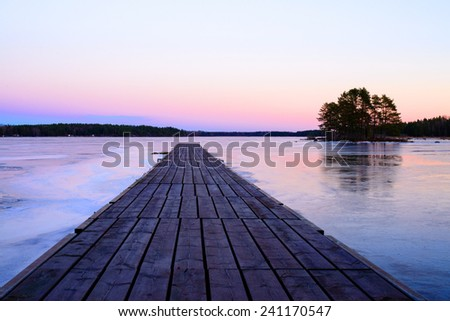 Bridge over frozen lake at sunset - stock photo