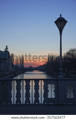 bridge over isar river munich with old lantern, sunset scenery - stock photo