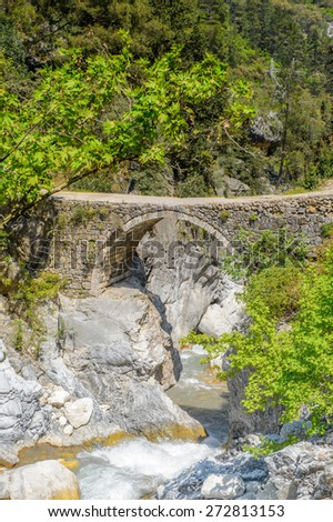 Bridge over the mountain river - stock photo