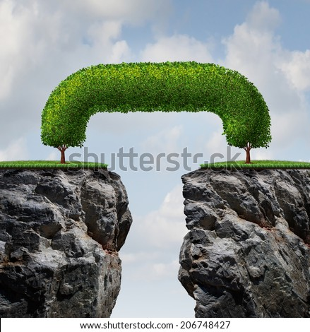 Bridge the gap business concept as two trees on a high steep cliff leaning towards each other bridging together to form a mutual connection as an icon of partnership success and growing together. - stock photo