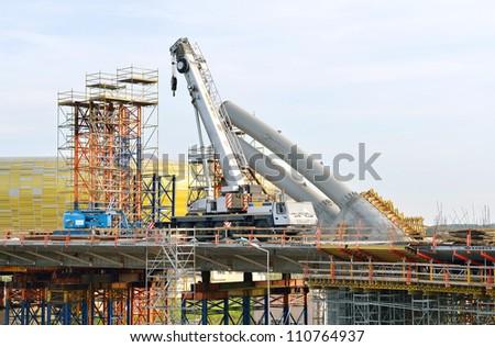 bridge under construction with crane and scaffolding - stock photo