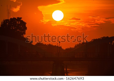Bridge with a beautiful cloudy sunset in the background.Lampang,Thailand - stock photo
