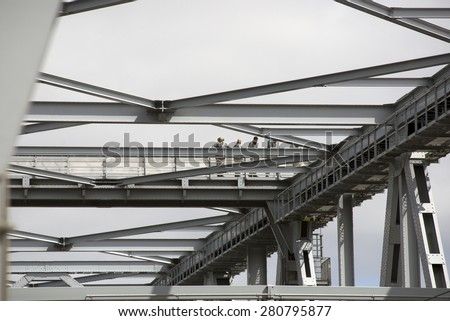 Bridge with bridge-walking bridge and small people in gray coveralls on top of the Old Little Belt Bridge. - stock photo