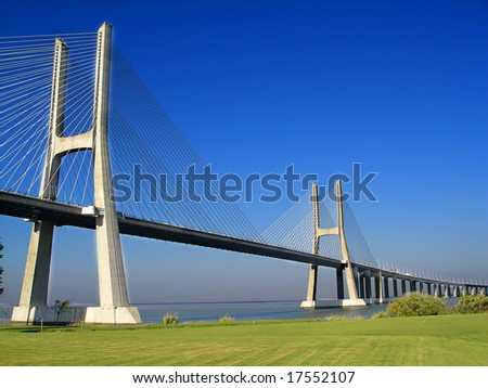 Bridge with green grass and blue sky - stock photo