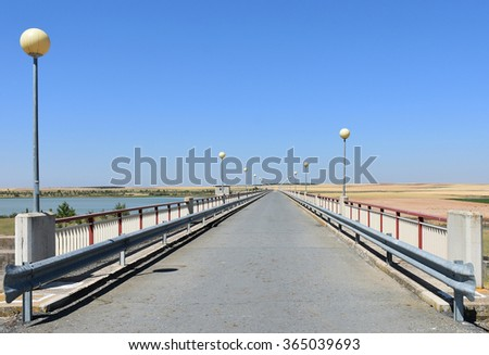 Bridge with street lights under a blue sky in the dam - stock photo