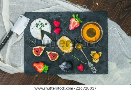 Brie cheese, fresh strawberries, figs, raspberries, ground cherry, thyme a slice of bread and a small bawl of honey with a tea-spoon on a dark stone board  - stock photo