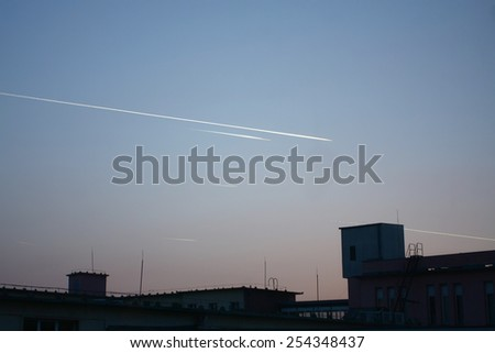 bright aircraft trails on sky at dusk behind building silhouette - stock photo