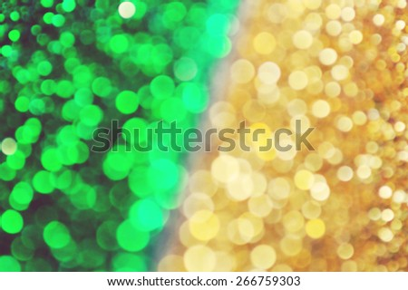 Bright and abstract blurred green and golden background with shimmering glitter - stock photo