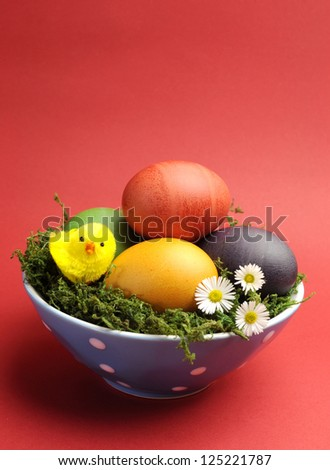 Bright and cheerful Happy Easter still life with rainbow color eggs in blue polka dot bowl against a red background. Portrait vertical orientation - stock photo