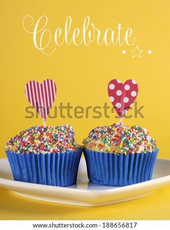 Bright and cheery red blue and yellow theme cupcakes with hundred and thousands candy topping and heart toppers for birthday or special occasion with sample Celebrate text or copy space. - stock photo